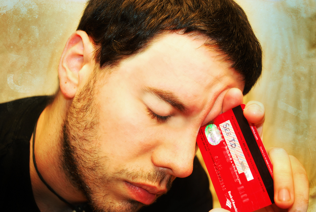 man with banking card (source Flickr from B Rosen)